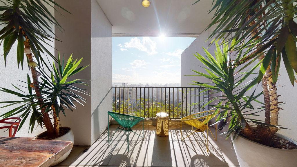Foto de varanda com plantas, duas cadeiras, uma bela vista da cidade e o sol brilhando forte