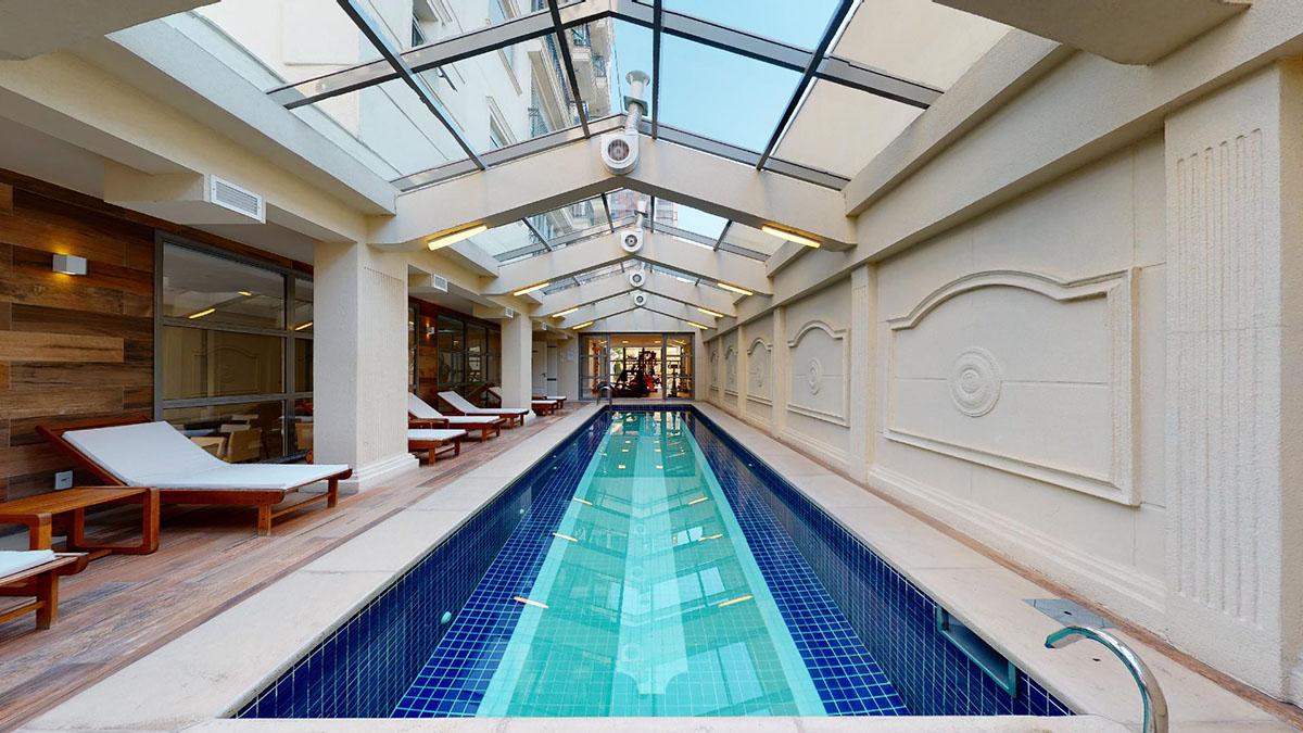 Imagem de uma bela e ampla piscina com espreguiçadeiras