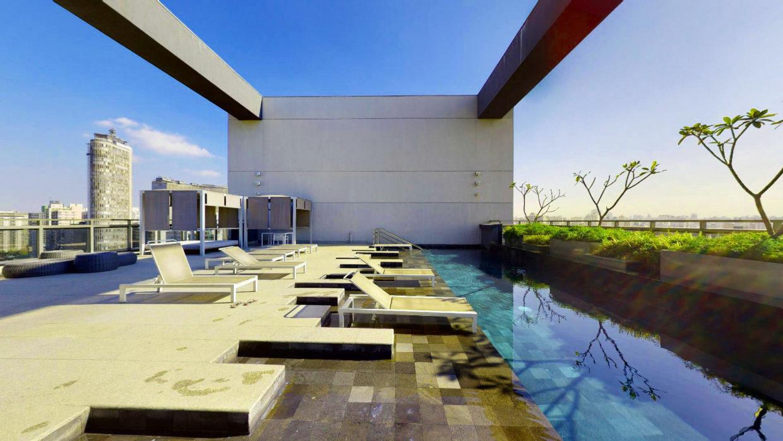 Imagem de piscina no andar alto de um prédio. O teto é aberto, há plantas e espreguiçadeiras nas bordas da piscina e uma bela vista da cidade.