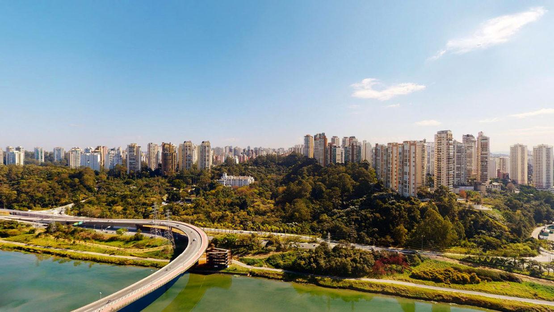 A cidade de São Paulo vista de um prédio no bairro Santo Amaro. Vê-se uma faixa de água com um viaduto sobre ela, muitas árvores e muitos prédios atrás delas, além de um belo céu azul.